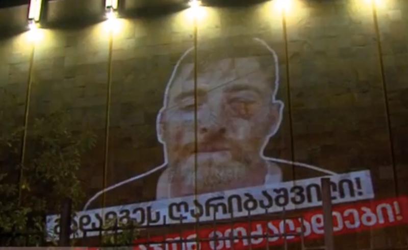 დაისაჯონ მოძალადეები - ლექსო ლაშქარავას გამოსახულება მთავრობის ადმინისტრაციის შენობაზე